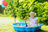 Happy little girl playing with sand in sunny garden — Stok fotoğraf