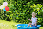 Happy little girl playing with sand in sunny garden — Photo