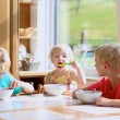 Group of happy kids having healthy breakfast sitting in sunny kitchen — Stock Photo #49487279