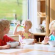 Group of happy kids having healthy breakfast sitting in sunny kitchen — Stock Photo #49487281