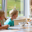 Group of happy kids having healthy breakfast sitting in sunny kitchen — Stock Photo #49487283