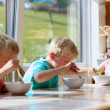 Group of happy kids having healthy breakfast sitting in sunny kitchen — Stock Photo #49487287