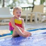 Happy little girl having fun in outdoors swimming pool — Stock Photo