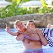 Father and son having fun in outdoors swimming pool — Stock Photo