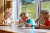 Group of happy kids having healthy breakfast sitting in sunny kitchen — Stock Photo