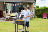 A man cooking meat on barbecue for summer family dinner at the backyard of the house — Foto de Stock