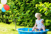 Happy little girl playing with sandbox outdoors  on a sunny summer day — Stock Photo