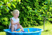 Happy little girl playing with sandbox outdoors  on a sunny summer day — Photo