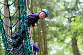 Cute school boy enjoying a sunny day in a climbing adventure activity park — ストック写真