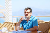 Handsome man drinking coffee sitting in cozy beach cafe — Stock Photo