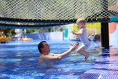 Happy father and little daughter having fun in outdoors swimming pool — Foto de Stock