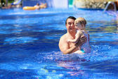 Happy father and little daughter having fun in outdoors swimming pool — Foto Stock