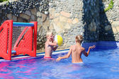Two happy boys playing with inflatable ball in swimming pool — Foto Stock