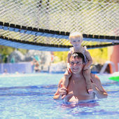 Father and daughter having fun in outdoors swimming pool — Stock Photo
