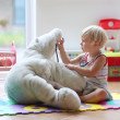 Little girl plays doctor providing healthcare to teddy bear — Stock Photo #49817017