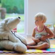 Little girl plays doctor providing healthcare to teddy bear — Stock Photo #49817023