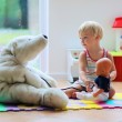 Little girl plays doctor providing healthcare to teddy bear — Stock Photo #49817025