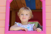 Happy little girl having fun in playhouse on a summer day — Stock Photo