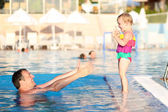 Father and daughter having fun in outdoors swimming pool — Stockfoto