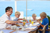 Family of four having healthy breakfast in outdoors cafe — Stock Photo