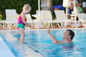 Father and daughter having fun in outdoors swimming pool — Foto Stock