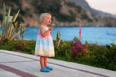 Little girl eating ice cream walking on beautiful promenade — Stock Photo