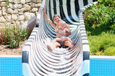 Mother and daughter having fun on slide in aqua park — Stock Photo