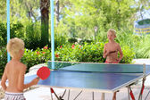 Two happy boys playing ping pong outdoors — Stock Photo