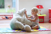 Little girl plays doctor providing healthcare to teddy bear — Stock Photo