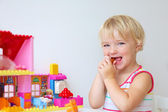 Happy little girl building house from colorful plastic blocks — Stock fotografie