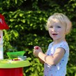 Happy toddler girl playing with toy kitchen outdoors — Stock Photo #49922195