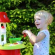 Happy toddler girl playing with toy kitchen outdoors — Stock Photo #49922211