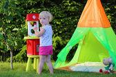 счастливый малыш девочка играет с игрушкой кухня на открытом воздухе — Стоковое фото