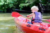 Active happy teenage boy kayaking on the river — Stock Photo