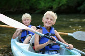 Two happy school boys kayaking on the river — Stock Photo