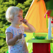Happy toddler girl playing with toy kitchen outdoors — Stock Photo