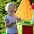 Happy toddler girl playing with toy kitchen outdoors — Stock Photo #50240385