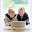 Two school boys working with laptop lying on the floor — Stock Photo #50845433