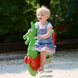 Happy little girl playing on spring horse in the park — Stock Photo #50845609
