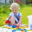 Funny little girl playing with toys outdoors — Stock Photo #50845679