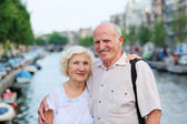 Happy senior couple enjoying canals in Amsterdam — Stock Photo