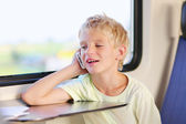 Young boy traveling by train talking on mobile phone — Stock Photo
