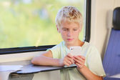 Young boy writing text message on his phone sitting in train — Stock Photo