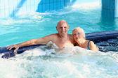 Happy senior couple relaxing in jacuzzi — Stock Photo