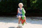 Happy little girl playing on spring horse in the park — Stock Photo