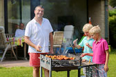 Father with kids preparing meat on barbecue in the garden — Stock Photo