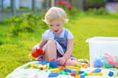 Funny little girl playing with toys outdoors — Stock Photo