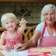 Grandmother making cookies with granddaughter — Stock Photo #51793349