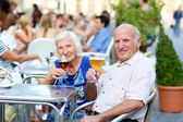 Senior couple drinking beer in outdoors cafe — Stock Photo