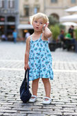 Cute little girl talking on mobile phone in the middle of the city — Stock Photo